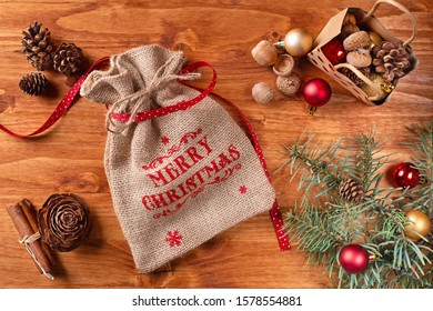 Merry Christmass written in red color font on a bag filled with christmass decorations arranged on a table top