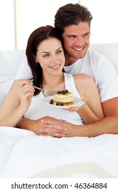 Merry couple having breakfast lying in the bed