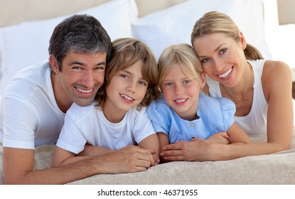 Merry family having fun lying on a bed