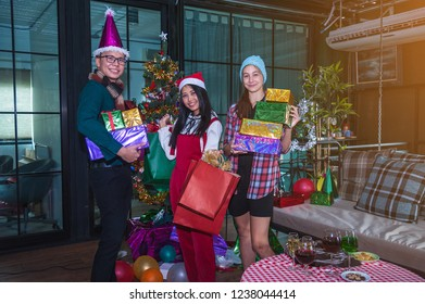 Merry family at home party. People drink champagne and exchange gifts. Between them is a guy dressed as Santa Claus. On the table are fruits and sweets. Family is having fun with X'Mas decoration.