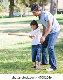 Merry father playing baseball with his son in the park