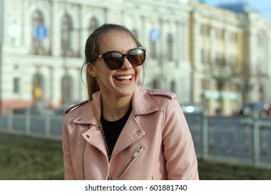 Merry girl contagiously laughs while walking around the city. She is dressed in a pink jacket and sunglasses.