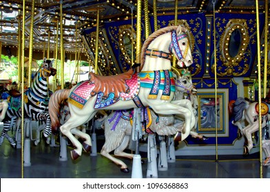 Merry go round has beautiful animals on it.  This carousel horse is decorated with pink, turquoise and blue.