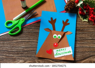 Merry greeting card with a Christmas deer on a wooden table. Handmade. Children's creativity project, crafts, crafts for kids.