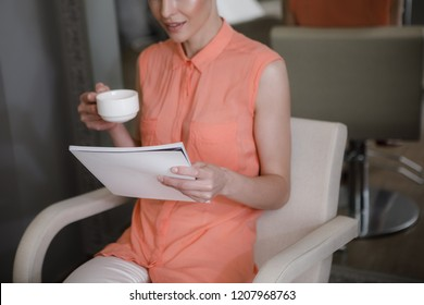 Merry lady is sitting in chair and reading journal. She is holding cup of coffee while spending time in beauty studio