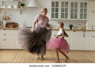 Merry leisure time. Happy energetic grandmother teach ball dance active little child. Caring grandma junior girl grandkid engaged in dancing in funny large fluffy skirts barefoot on warm kitchen floor
