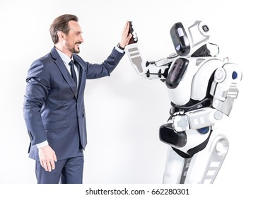 Merry male person making friends with cyborg