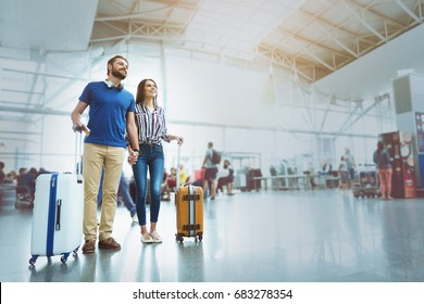 Merry smiling couple waiting for plane
