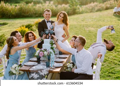 Merry wedding in nature. Guests with the bride and groom are celebrating at the table. Wedding fiancee of the bride and groom with friends