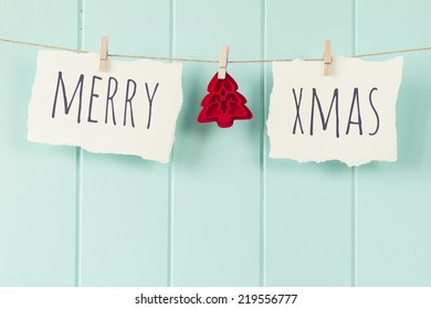 """""""Merry xmas"""" and a felt tree hanging on a rope with clothespins. A robin egg blue wainscot as background. Vintage Style."""