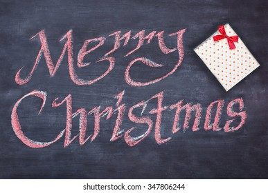Merry Xmas greeting handwritten on a small slate chalkboard