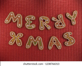 Merry Xmas greeting made of gingerbread cookies decorated with icing on red knitted wool fabric background