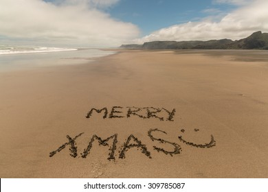 merry xmas handwritten in sand