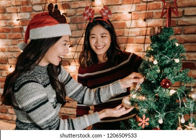merry xmas and happy new year are coming. sisters decorating the christmas tree together at home. young girls cheerful preparing for christmas eve concept.