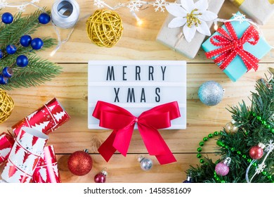 Merry xmas words on light box and ribbon surrounded by christmas tree, gift, ornaments with christmas lights on wooden table. Flatlay.