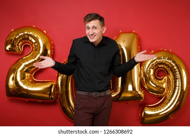 Merry young man in black shirt celebrating holiday party standing spreading hands isolated on bright red background, golden numbers air balloons studio portrait. Happy New Year 2019 Christmas concept