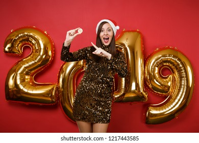 Merry young Santa girl in shiny glitter dress, Christmas hat hold bitcoin isolated on bright red wall background, golden numbers balloons studio portrait. Happy New Year 2019 holiday party concept