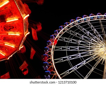 Merry-go-round in motion and big wheel glowing in the background, funfair by night, beer fest at Stuttgart, Germany.