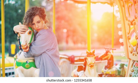 Merry-go-round young romantic women playing on carousel. Retro vintage nostalgia childhood concept.