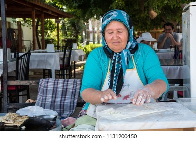 Mersin, Turkey - June 14, 2018: A eldery turkish woman preparing traditional turkish unleavened bread.