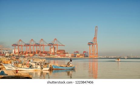 MERSIN, TURKEY, NOVEMBER 1, 2018: Small fishing boats floating at coast, Mersin International Port at the background.Mersin is a large city and a port on the Mediterranean coast of southern Turkey.