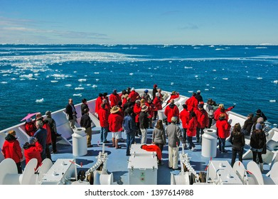 """Mertz Glacier, Antarctica - January 3 2010: Passengers view the broken ice & bergy bits off the glacier from the bow of the small ship """"Orion"""""""