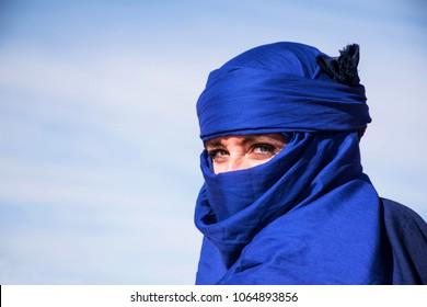 Merzouga, Morocco -  03-01-2018: portrait young woman with indigo blue scarf. Nomad turban, touareg scarf. Blue sky background. Sahara, desert turban. Bright blue.