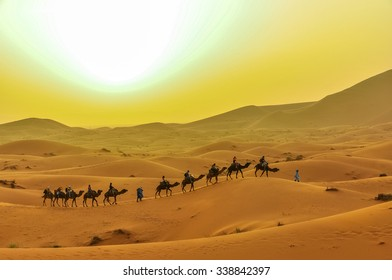 MERZOUGA, MOROCCO, APRIL 13, 2015: Tourists take part in camels trip on sand dunes of Erg Chebbi at sunset
