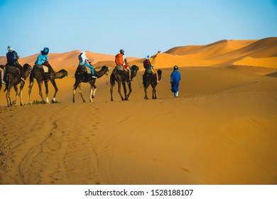 Merzouga, Morocco - APRIL 29 2019: Tourists on a camel ride tour in Sahara Desert