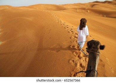 MERZOUGA, MOROCCO - August 23: A Berber male guide in traditional dress leading a camel through the Erg Chebbi sand dunes in the Sahara Desert near Merzouga, Morocco on the 23rd August, 2015.