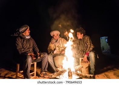 Merzouga, Morocco - December 29, 2017: Berbers at camp fire in Sahara desert near Merzouga village, Morocco.