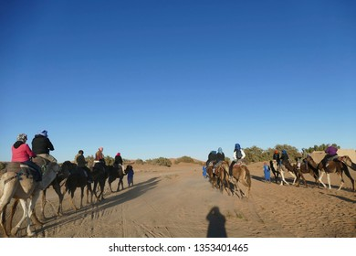 MERZOUGA, MOROCCO - FEB 15, 2019 - ourists mount camels for a ride in the Sahara Desert near Merzouga, Morocco, Africa
