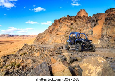 Merzouga, Morocco - Feb 21, 2016: blue Polaris RZR 800 crossing a mountain road in the Moroccan desert near Merzouga. Merzouga is famous for its dunes, the highest in Morocco.