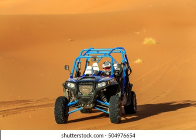 Merzouga, Morocco - Feb 22, 2016: Blue Polaris RZR 800 and pilot in Morocco desert near Merzouga. Merzouga is famous for its dunes, the highest in Morocco.