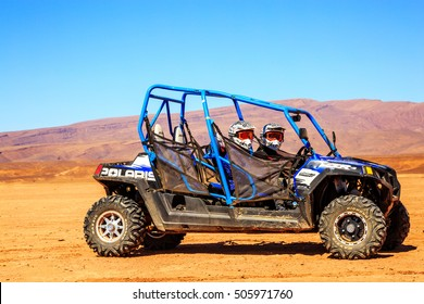 Merzouga, Morocco - Feb 22, 2016: Side view on blue Polaris RZR 800 with it's pilots in Morocco desert near Merzouga. Merzouga is famous for its dunes, the highest in Morocco.