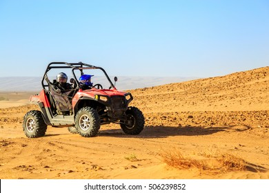 Merzouga, Morocco - Feb 22, 2016: front view on blue Polaris RZR 800 with it's pilots in Morocco desert near Merzouga. Merzouga is famous for its dunes, the highest in Morocco.