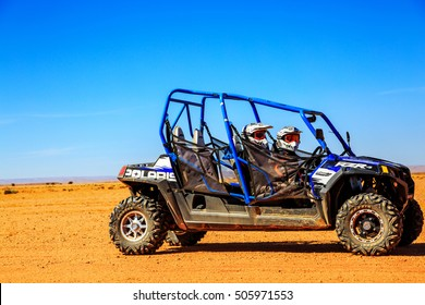 Merzouga, Morocco - Feb 23, 2016: Side view on blue Polaris RZR 800 with it's pilots in Morocco desert near Merzouga. Merzouga is famous for its dunes, the highest in Morocco.