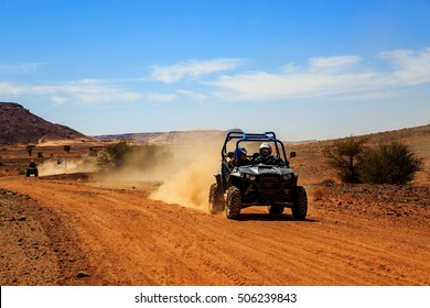 Merzouga, Morocco - Feb 23, 2016: front view on blue Polaris RZR 800 with it's pilots in Morocco desert near Merzouga. Merzouga is famous for its dunes, the highest in Morocco.
