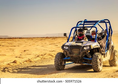 Merzouga, Morocco - Feb 24, 2016: front view on blue Polaris RZR 800 with it's pilots in Morocco desert near Merzouga. Merzouga is famous for its dunes, the highest in Morocco.