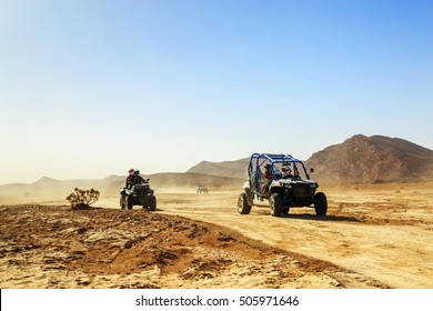 Merzouga, Morocco - Feb 24, 2016: convoy of off-road vehicles (RZR, Quad and motorbikes) in Morocco desert near Merzouga. Merzouga is famous for its dunes, the highest in Morocco.