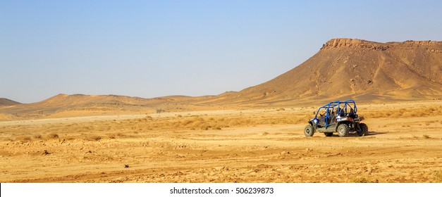 Merzouga, Morocco - Feb 24, 2016: panoramic view on blue Polaris RZR 800 with it's pilots in Morocco desert near Merzouga. Merzouga is famous for its dunes, the highest in Morocco.