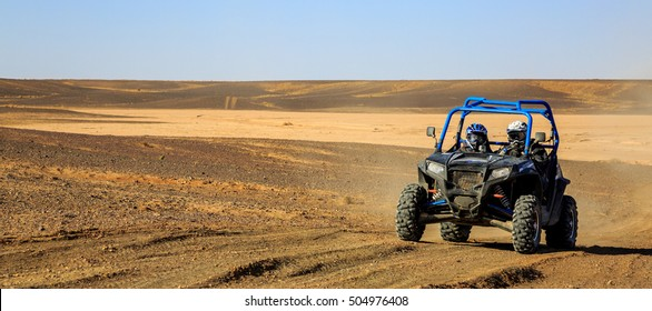 Merzouga, Morocco - Feb 25, 2016: Panoramic view of Blue Polaris RZR 800 and pilots in Morocco desert near Merzouga. Merzouga is famous for its dunes, the highest in Morocco.