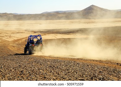 Merzouga, Morocco - Feb 25, 2016: back view on blue Polaris RZR 800 with it's pilot in Morocco desert near Merzouga. Merzouga is famous for its dunes, the highest in Morocco.