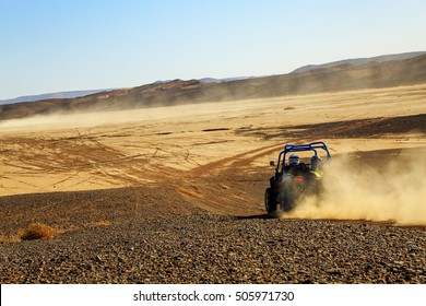 Merzouga, Morocco - Feb 25, 2016: back view on blue Polaris RZR 800 with it's pilots in Morocco desert near Merzouga. Merzouga is famous for its dunes, the highest in Morocco.