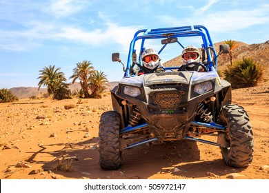 Merzouga, Morocco - Feb 26, 2016: front view on blue Polaris RZR 800 with it's pilots in Morocco desert near Merzouga. There is a palm grove in the background