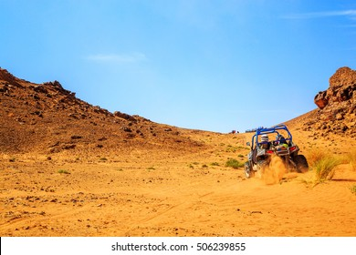 Merzouga, Morocco - Feb 26, 2016: back view on great canyon with blue Polaris RZR 800 in Morocco desert near Merzouga. Merzouga is famous for its dunes, the highest in Morocco.