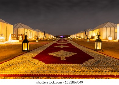 Merzouga / Morocco - February 19 2019: Main path accross the tents and the lanterns of Golden Camp site in Sahara Desert (Merzouga), Morocco during night time
