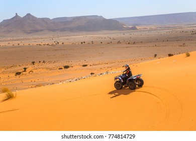 Merzouga, Morocco - February 26, 2016: Unidentified person and pilot riding a RZR800 in Merzounga desert in Morocco. Merzouga is famous for its dunes, the highest in Morocco.