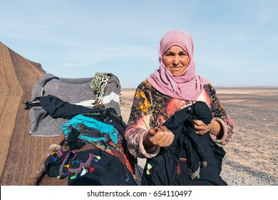 MERZOUGA, MOROCCO - JANUARY 8, 2017: Berber nomad woman sells self-made embroidered clothes in her camp in the desert near Merzouga.