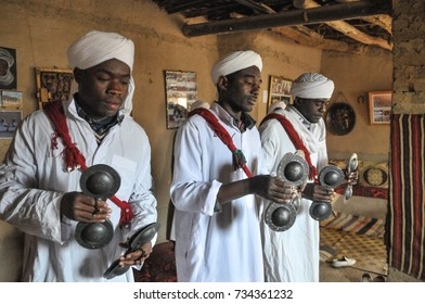 MERZOUGA, MOROCCO - MARCH 20, 2012: Gnawa men dancing and singing inside a house in the village of Khamlia near the Erg Chebbi desert